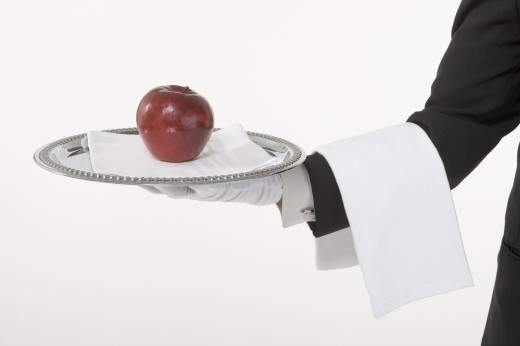 Butler holding a silver tray with an apple : Stock Photo