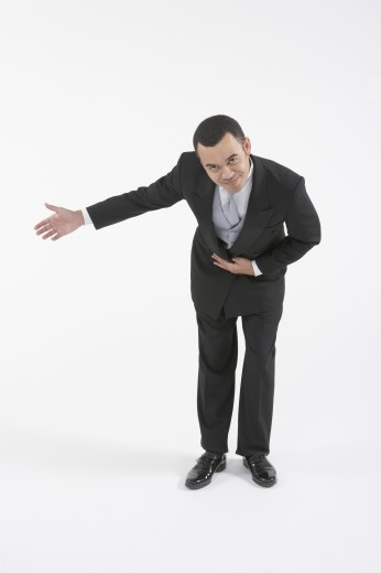 Asian butler bowing and making a welcoming gesture : Stock Photo