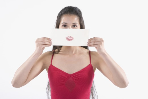 Stock Photo: 1589R-24287 Young Hispanic woman holding a piece of paper with a lipstick imprint in front of her face