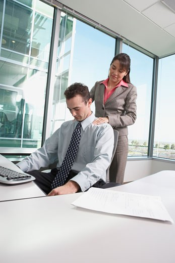 Stock Photo: 1589R-24295 Hispanic businesswoman giving Hispanic businessman a shoulder massage in his cubicle, Redwood City, California, United States,