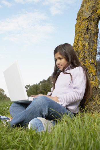 Girl with laptop sitting against tree : Stock Photo