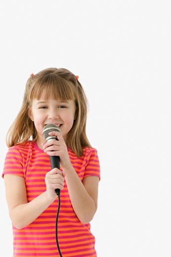 Stock Photo: 1589R-24479 Studio shot of young girl singing with a microphone