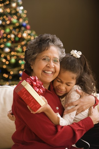 Hispanic grandmother hugging granddaughter with Christmas gift : Stock Photo