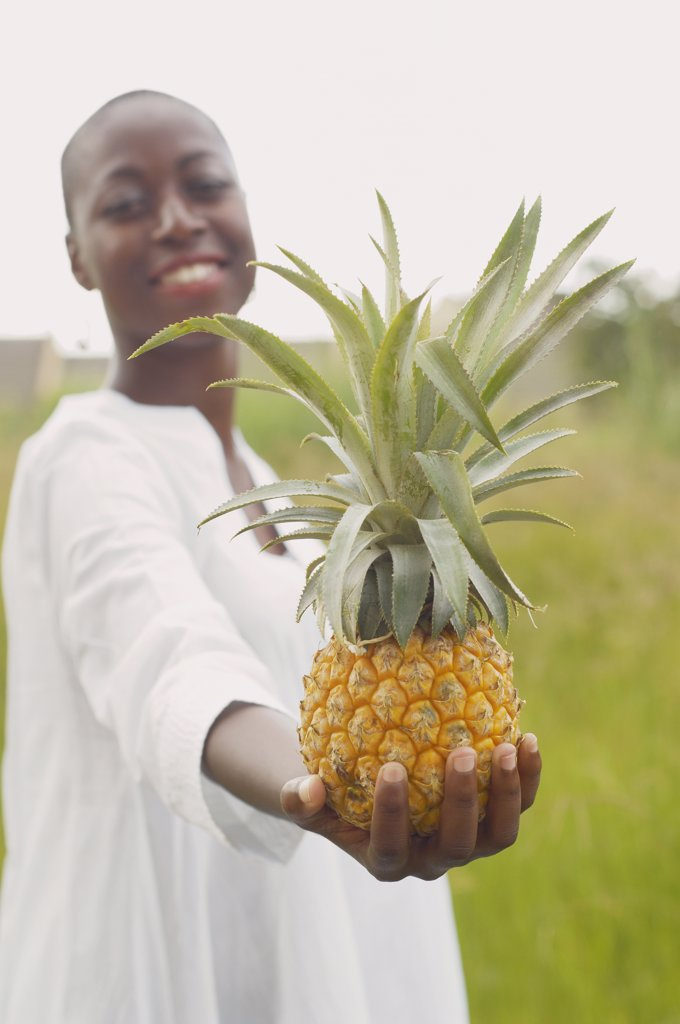 African American woman holding pineapple outdoors : Stock Photo