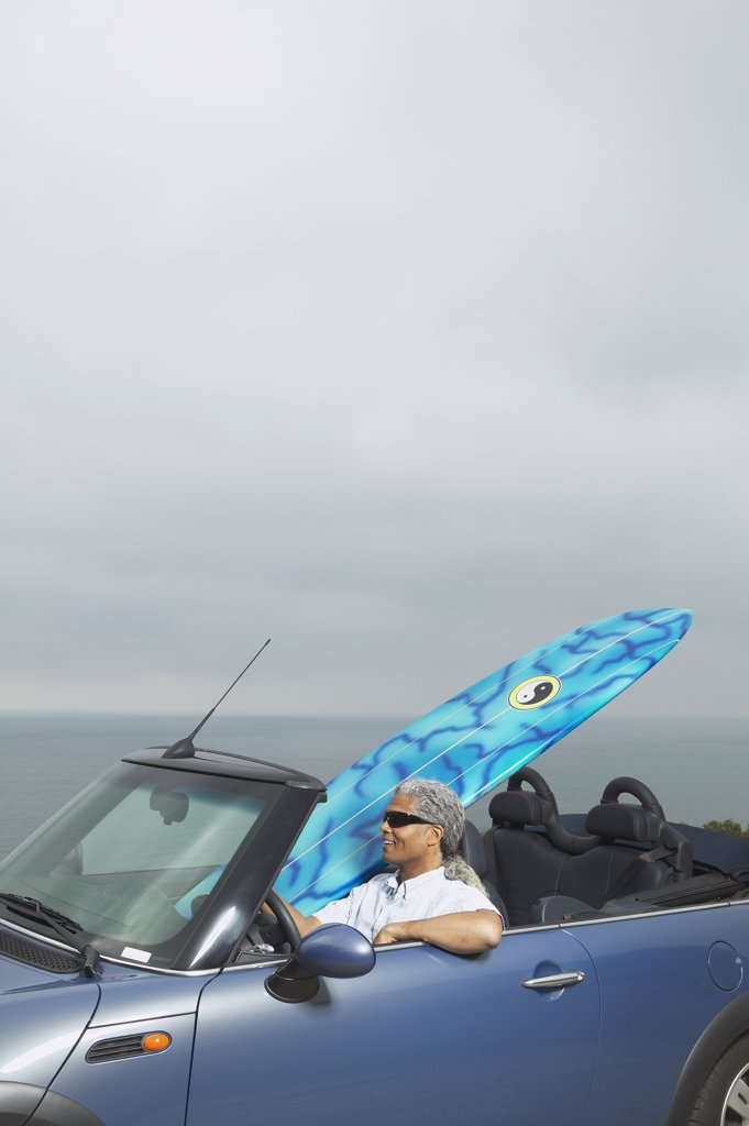 Stock Photo: 1589R-24926 Senior man driving a convertible with a surfboard in it, Oakland, California, United States