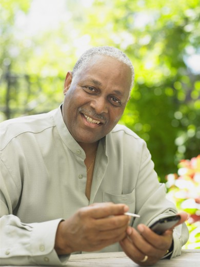 Middle-aged African man using his electronic organizer, Toronto, Canada : Stock Photo