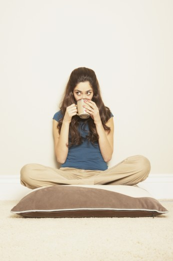Stock Photo: 1589R-25053 Young Hispanic woman sitting cross-legged on a floor pillow drinking coffee, San Rafael, California, United States
