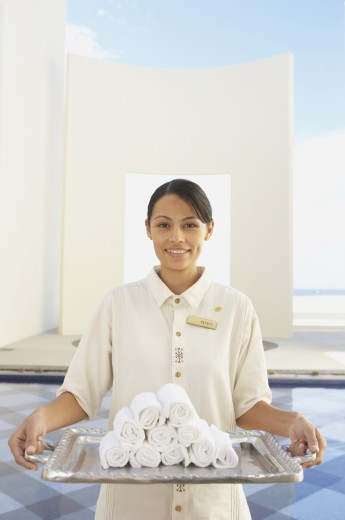 Hotel employee holding silver tray with rolled up towels, Los Cabos, Mexico : Stock Photo