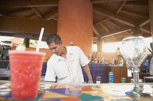 Stock Photo: 1589R-25209 Drinks on a bar with bartender in background, Los Cabos, Mexico