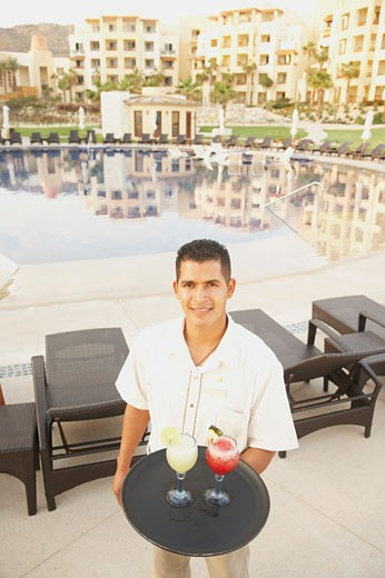 Stock Photo: 1589R-25214 Hispanic male waiter with a tray of drinks, Los Cabos, Mexico