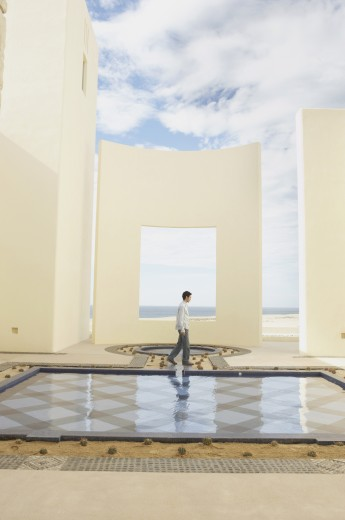 Stock Photo: 1589R-25219 Man walking past luxury hotel pool, Los Cabos, Mexico