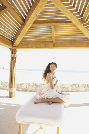 Stock Photo: 1589R-25261 Woman sitting on massage table outdoors, Los Cabos, Mexico