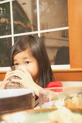 Stock Photo: 1589R-25478 Young Asian girl drinking water at the table, San Rafael, California, United States