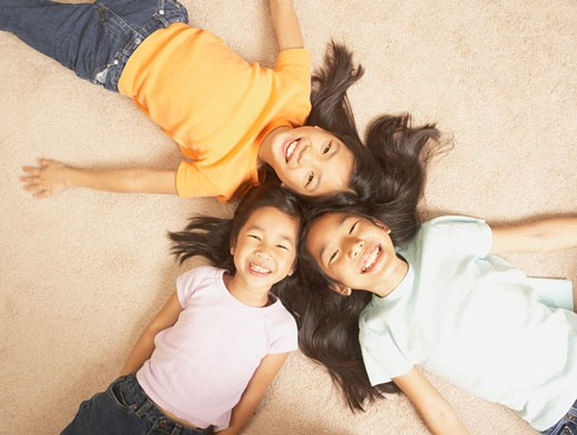 Three young Asian sisters lying on the floor with their heads together, San Rafael, California, United States : Stock Photo