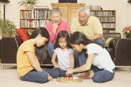 Stock Photo: 1589R-25490 Three young Asian sisters playing chinese checkers while grandparents watch, San Rafael, California, United States