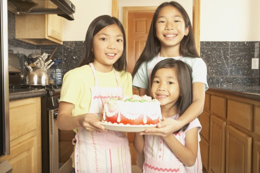 Stock Photo: 1589R-25494 Three young Asian sisters holding a cake in the kitchen, San Rafael, California, United States