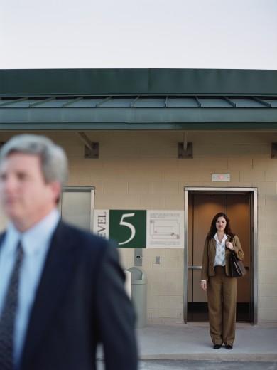 Businesswomen next to elevator at parking garage, Dallas, Texas, United States : Stock Photo