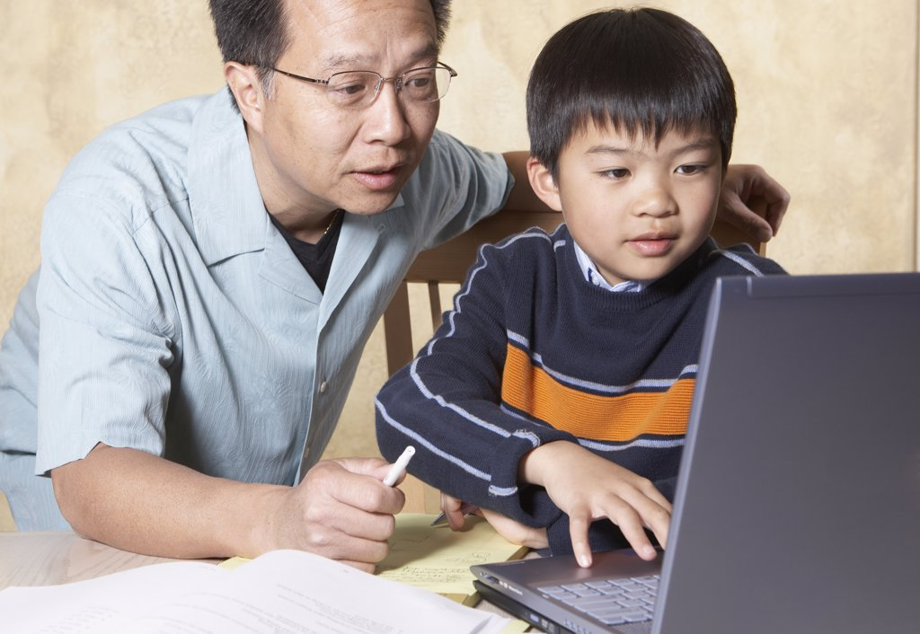 Stock Photo: 1589R-25927 Asian father helping young son with homework