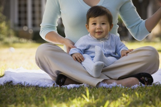 Hispanic baby sitting in mother's lap outdoors : Stock Photo