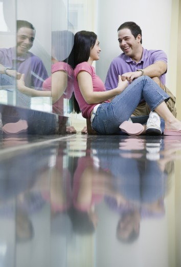 Couple sitting on reflective floor holding hands : Stock Photo