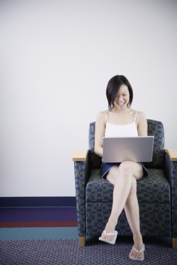 Young Asian woman smiling and using laptop : Stock Photo