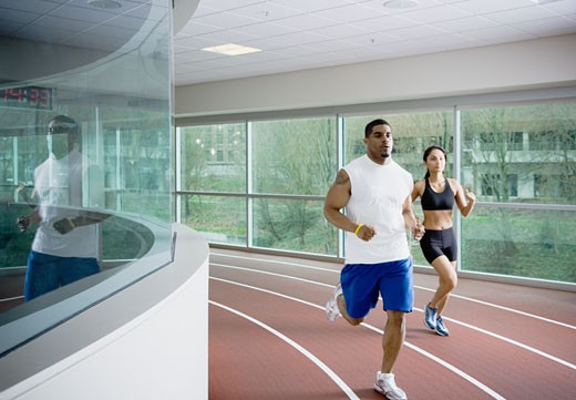 Stock Photo: 1589R-26473 Man and woman running on indoor track