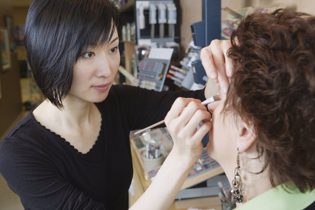 Stock Photo: 1589R-26677 Asian female make up artist performing make over in salon