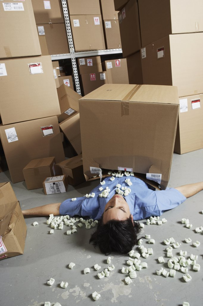 Stock Photo: 1589R-26726 Male warehouse worker laying under fallen box with packing peanuts