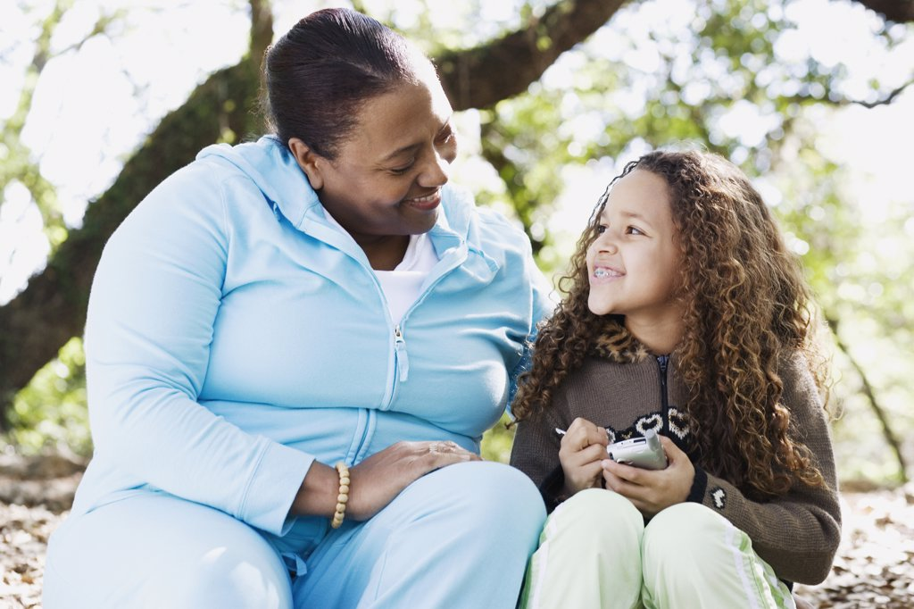 African mother and daughter smiling at each other outdoors : Stock Photo