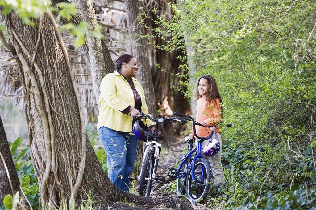 Stock Photo: 1589R-26819 African mother and daughter with bicycles in woods