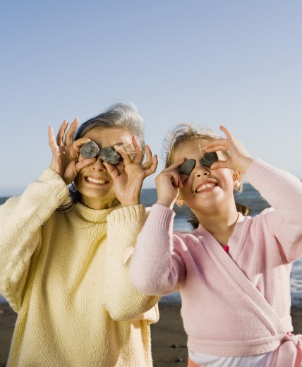 Grandmother and granddaughter holding up rocks to eyes at beach : Stock Photo