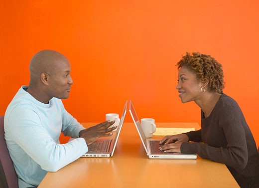 African couple using laptops at table : Stock Photo