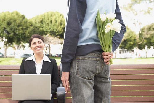 Stock Photo: 1589R-27202 Man with flowers behind back next to businesswoman on bench outdoors