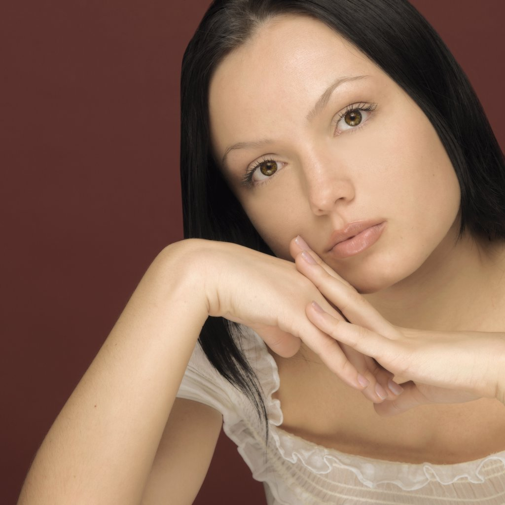 Studio shot of woman leaning face on hands : Stock Photo