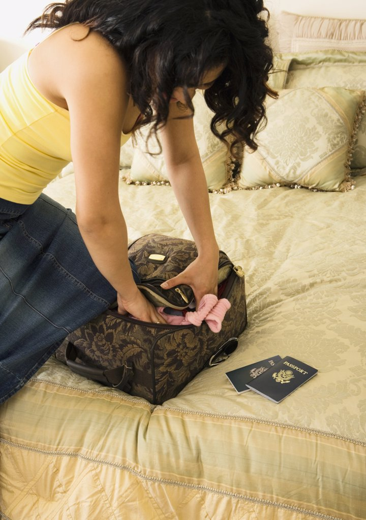 Stock Photo: 1589R-27290 Woman packing suitcase on bed