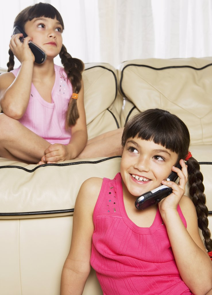 Hispanic sisters using cell phones on sofa : Stock Photo
