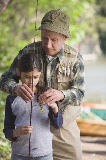 Hispanic grandfather helping granddaughter with fishing pole : Stock Photo