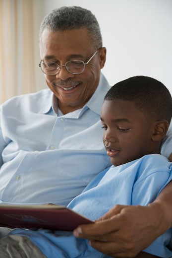 Stock Photo: 1589R-27416 African grandfather reading to grandson