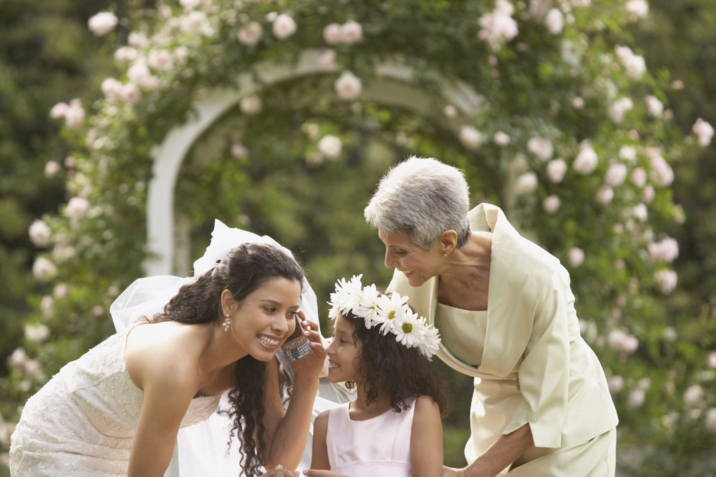 Stock Photo: 1589R-27639 Hispanic bride using cell phone with young girl and mother
