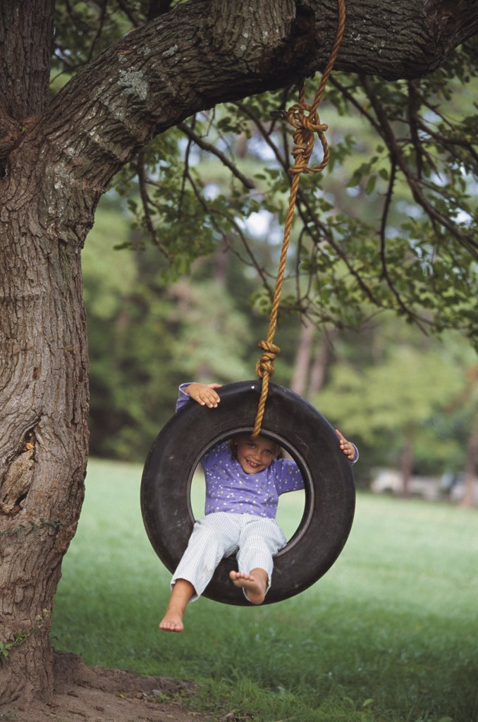 Stock Photo: 1589R-27671 Young girl sitting in tire swing