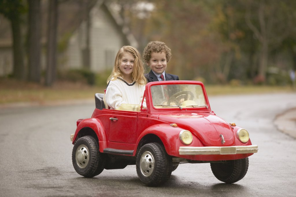 Stock Photo: 1589R-27700 Young boy and girl riding in toy car