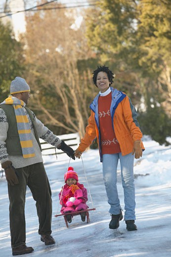 African couple pulling child on sled : Stock Photo