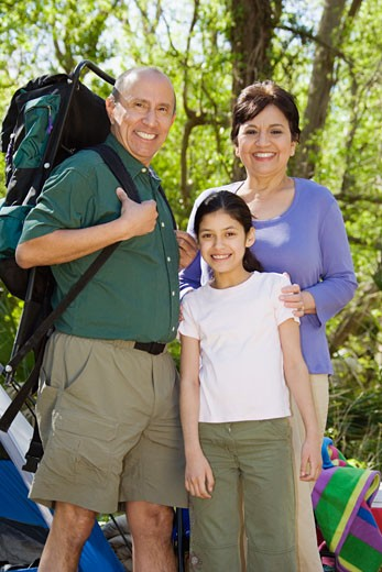 Hispanic grandparents and granddaughter camping : Stock Photo