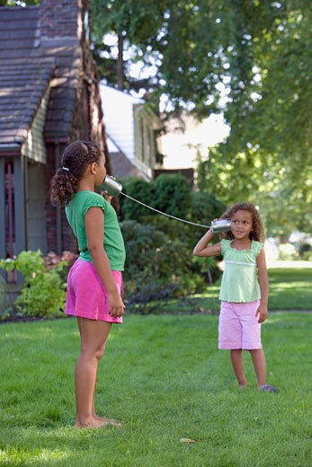 Stock Photo: 1589R-27949 Young African sisters playing telephone with two cans on the end of string outdoors
