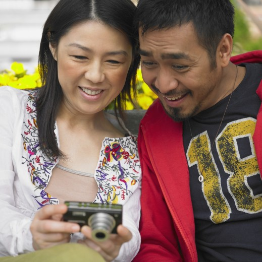 Stock Photo: 1589R-28092 Asian couple looking at digital camera and smiling