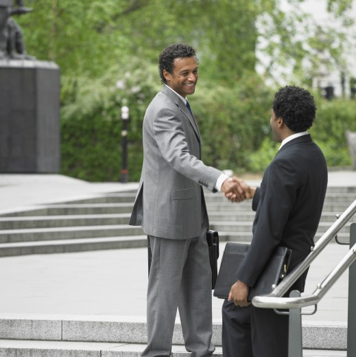 Two businessmen shaking hands on stairs outdoors : Stock Photo