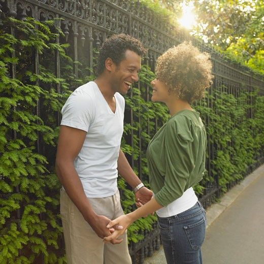 African couple smiling at each other outdoors : Stock Photo