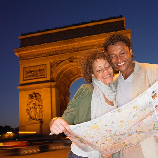 Couple looking at map in Paris at night : Stock Photo