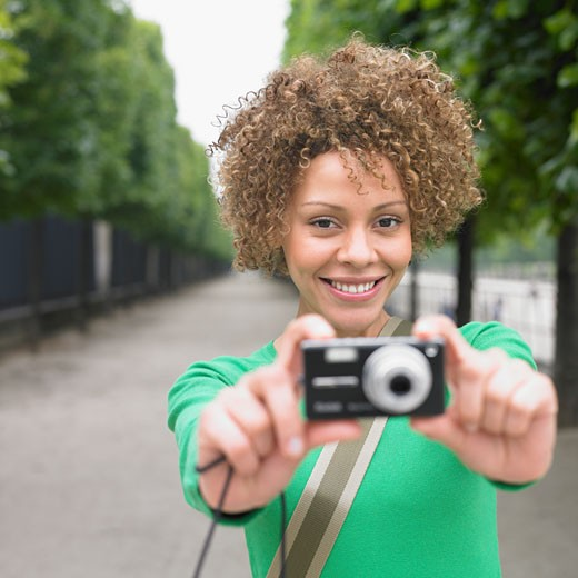 Stock Photo: 1589R-28181 African woman holding camera in outstretched hands outdoors
