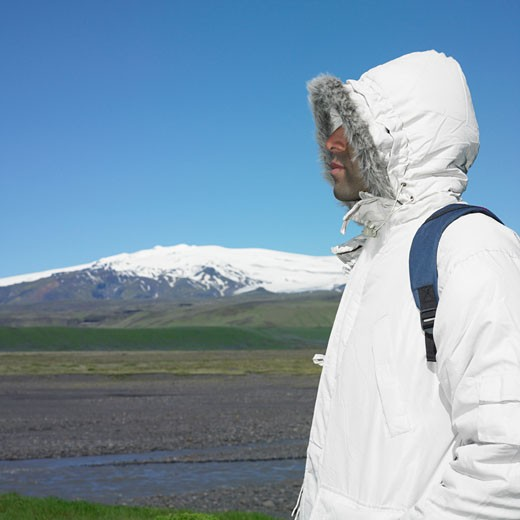 Stock Photo: 1589R-28205 Man wearing winter jacket and backpack with snow-capped mountain in background